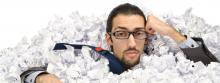 man under stacks of paper
